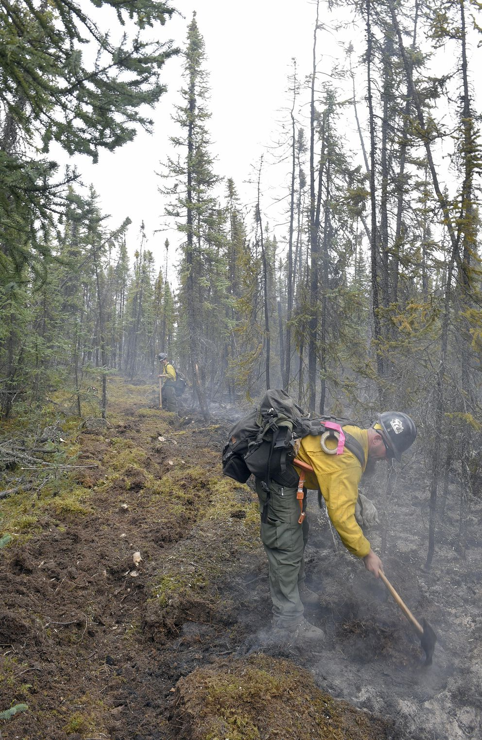 Members of the Tanana Chiefs Initial Attack Crew improve a saw line along the edge of the North Robertson fire on Friday. Burning along the Alaska Highway about 30 miles northwest of Tok, the fire had been reported to Alaska Division of Forestry on Thursday. Sam Harrel/Alaska DNR/Division of Forestry