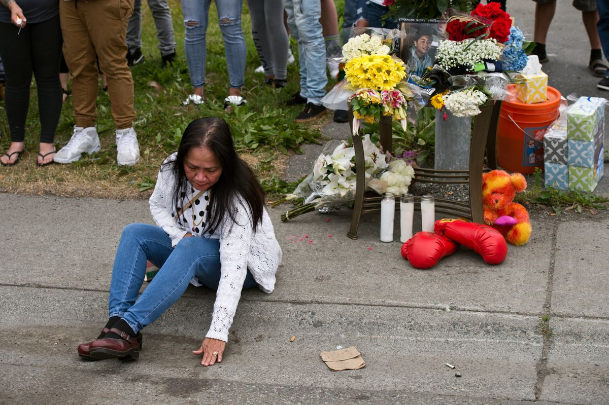 Fe Paller Bagunas, Raynaldo Khotesouvan's grandmother,  touches the pavement where Khotesouvan died. (Marc Lester / ADN)