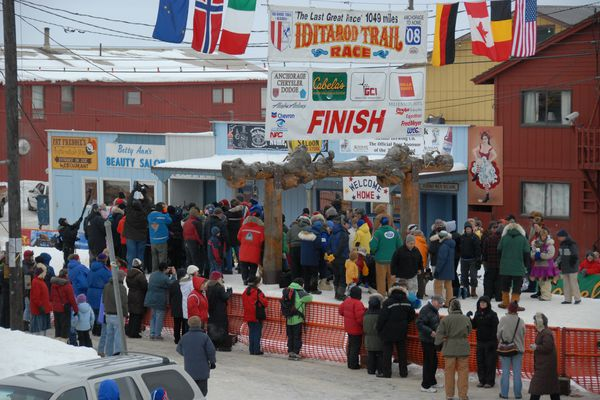 Iditarod sled dog musher Melissa Owens of Nome arrived back home to finish 30th Thursday afternoon March 13, 2008 crossing under the burled arch in Nome, AK. Melissa Owens is surrounded by media and fans after she finished the race. (Bob Hallinen / Anchorage Daily News)