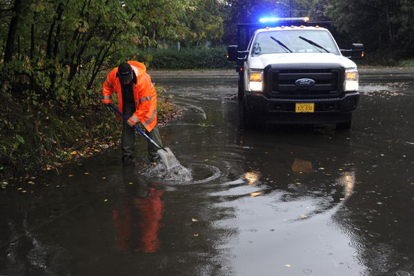 A city street maintenance worker clears leaves from a storm drain at West 18th Avenue and Arctic Boulevard during the rainstorm in Anchorage on Wednesday, Sept. 18, 2019. (Bill Roth / ADN)