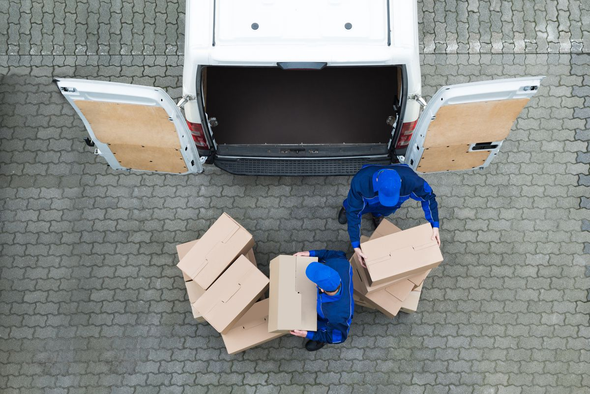 Directly above shot of delivery men unloading cardboard boxes from truck on street. (Thinkstock)