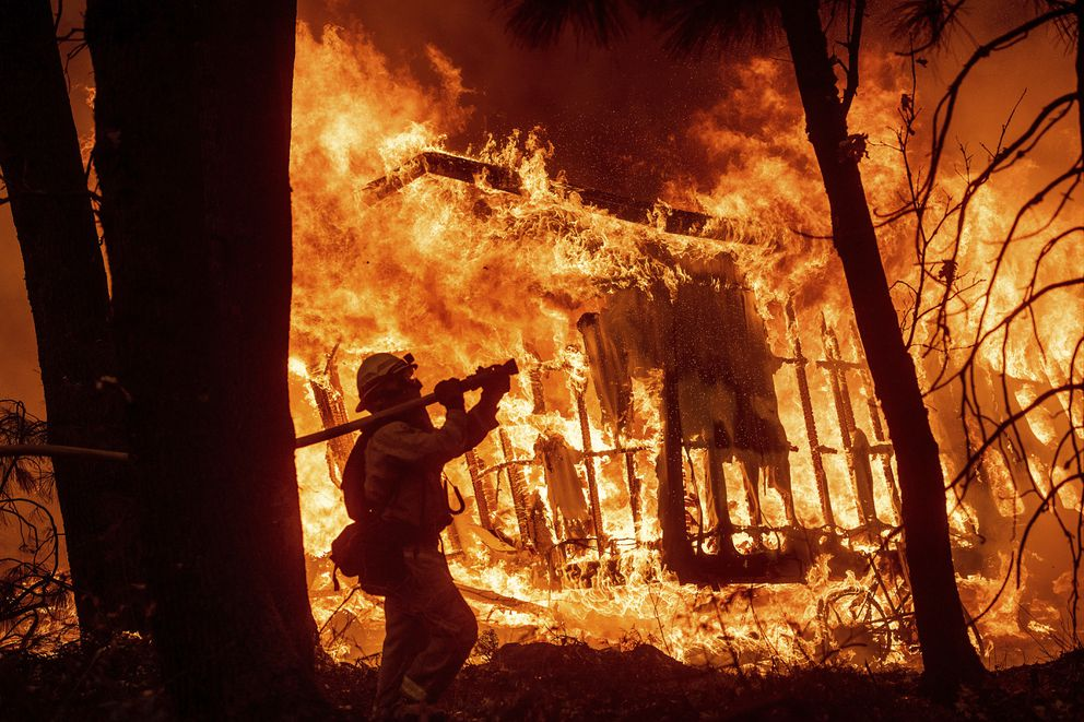 FILE - In this Nov. 9, 2018 file photo, firefighter Jose Corona sprays water as flames from the Camp Fire consume a home in Magalia, Calif. A massive new federal report warns that extreme weather disasters, like California's wildfires and 2018's hurricanes, are worsening in the United States. The White House report quietly issued Friday, Nov. 23 also frequently contradicts President Donald Trump. (AP Photo/Noah Berger, File)