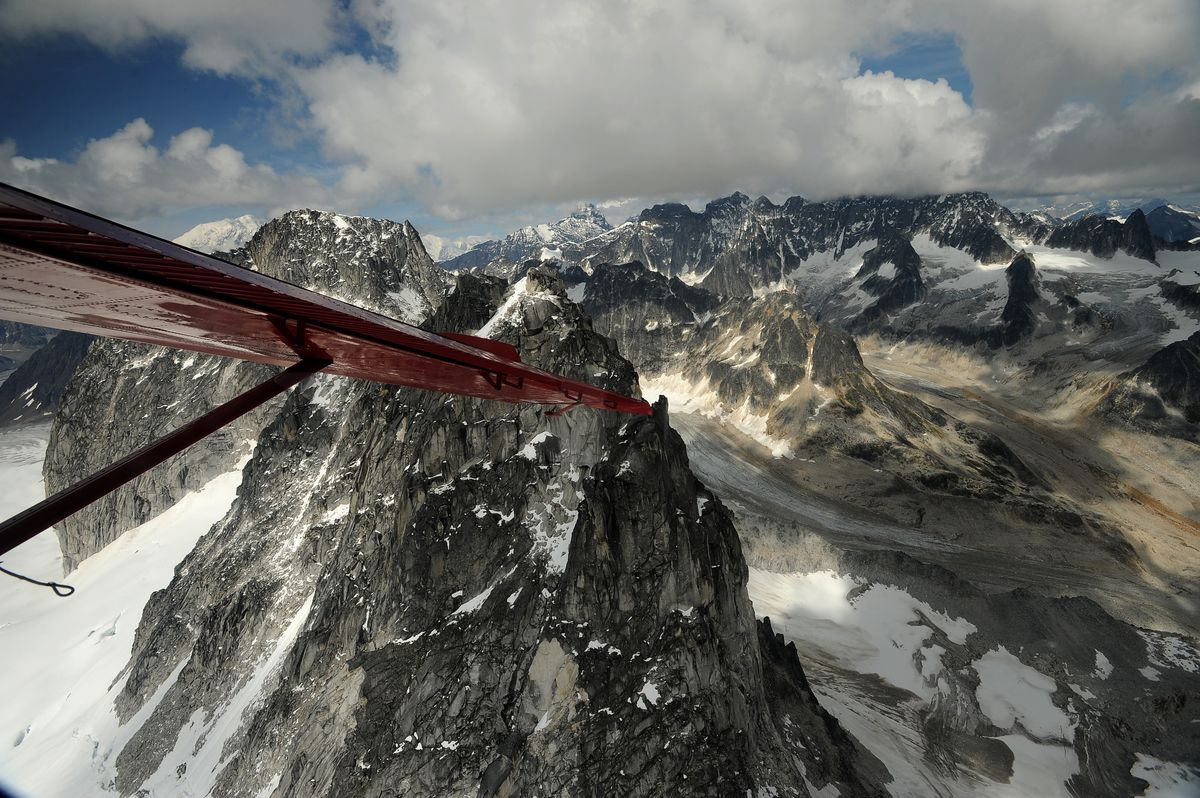 Little Switzerland is seen under a cloud layer as Talkeetna Air Taxi pilot Kris Peterson flies a Beaver airplane on a flightseeing tour of Mount McKinley and the peaks and glaciers on the south side of the mountain on Tuesday, July 21, 2015. Talkeetna Air Taxi is based out of Talkeetna, and flies daily tours of the mountain in Denali National Park.