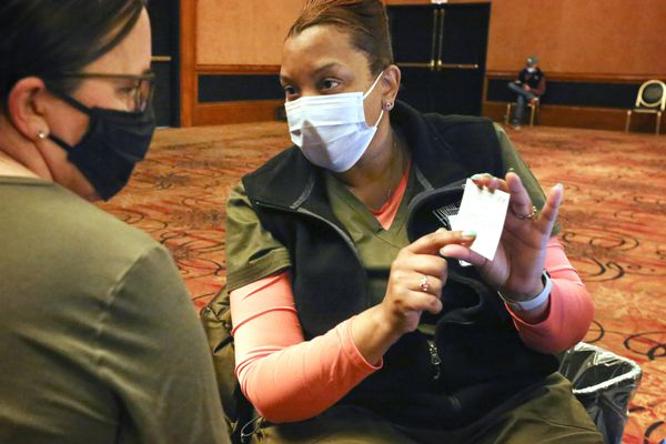Registered nurse Shawnece Stovall explains the vaccination card to Carmen Jones before she administers Jones' first dose of the Pfizer-BioNTech COVID-19 vaccine at a clinic set up in the Discovery Ballroom at Hotel Captain Cook in downtown Anchorage on Wednesday, March 24, 2021. The clinic will open again for walk-ins and those with appointments from 8 a.m. to 6 p.m., March 27-28. Appointments for the first dose of the Pfizer-BioNTech COVID-19 vaccine can be found at www.anchoragecovidvaccine.org or by contacting the state call center at 907-646-3322 and requesting the