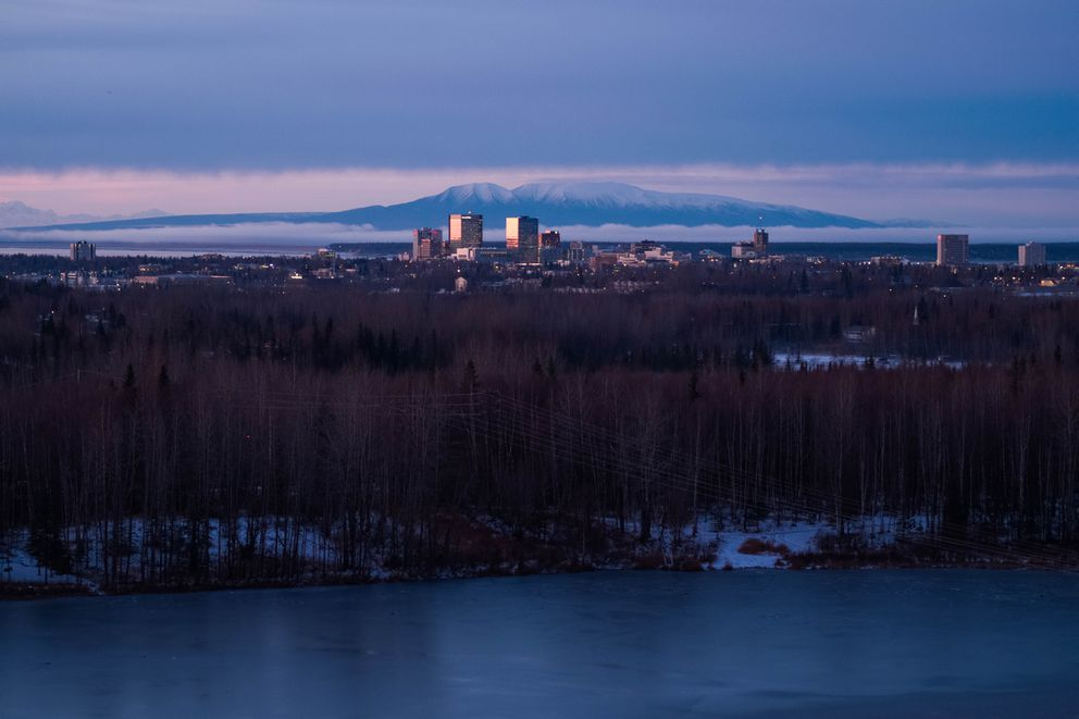 Buildings in downtown Anchorage are illuminated by the setting sun in 2018, in a view from Goose Lake. (Loren Holmes / ADN)