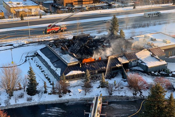 The former restaurant, Sea Galley, continues to burn Thursday afternoon, Jan. 3, 2019. The fire began early Thursday morning. The photograph is made from the Alaska USA Federal Credit Union building at 4000 Credit Union Dr. (Photo by Geoff Lundfelt)