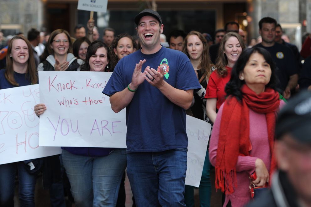Anchorage firefighter/paramedic Ben Schultz reacts to family and friends gathered to welcome him home at the airport on Thursday, May 24, 2018, nearly a year after falling from a ladder during a training accident at Station 5. Schultz who was in critical condition after the fall on June 5, 2017, was taken by fellow firefighters to Providence Alaska Medical Center where he spent four weeks in intensive care before being flown to rehabilitation at Craig Hospital in Denver for a traumatic brain injury. Schultz said he was surprised by the greeting at the airport and is excited to get back to work in a couple weeks under light duty. (Bill Roth / ADN)