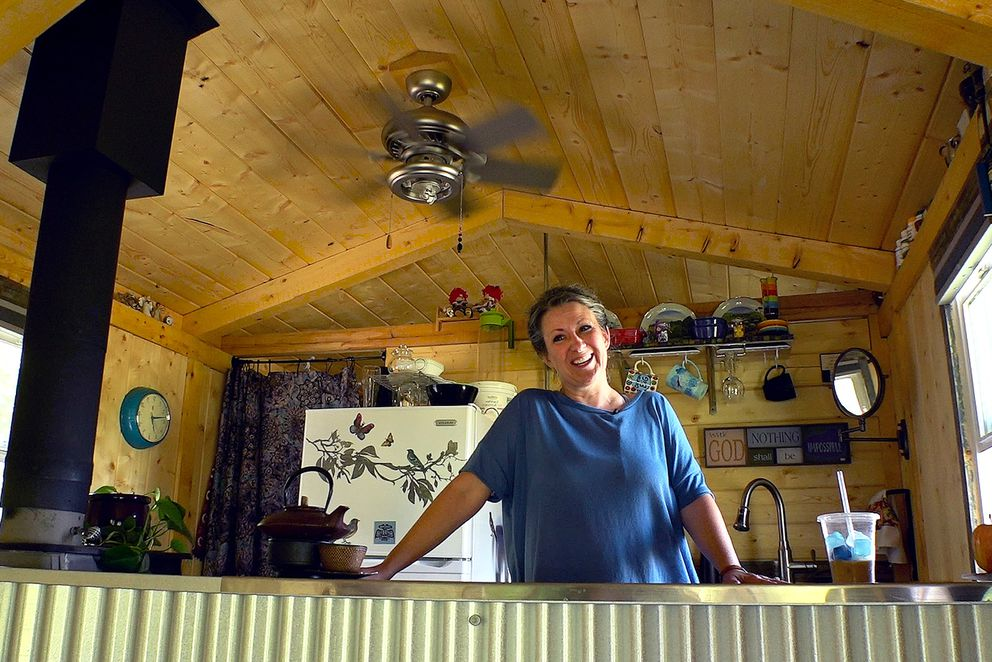 "Deborah Schaffer stands in the kitchen of her tiny house. A primary motivation for downsizing from a full-sized home last year was easier cleaning. ""I don't see the point in dusting,"" she said with a laugh. (Scott Jensen / Alaska Dispatch News)"