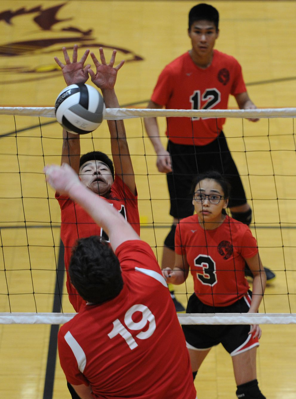 Gustavus sophomore David Shatswell (19) hits the ball toward Akiuk junior Nikolai Charles during pool play in the Mix Six state volleyball championships. (Bill Roth / ADN)