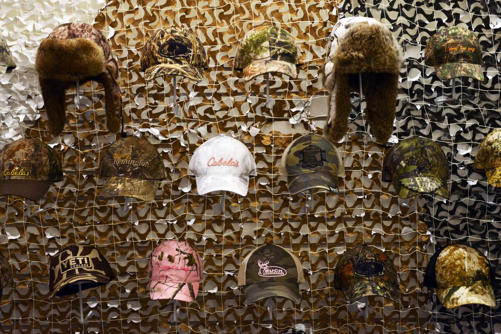 "Hunting hats fill a wall at the ""Camouflage: In Plain Sight"" exhibition. (Erik Hill / Alaska Dispatch News)"