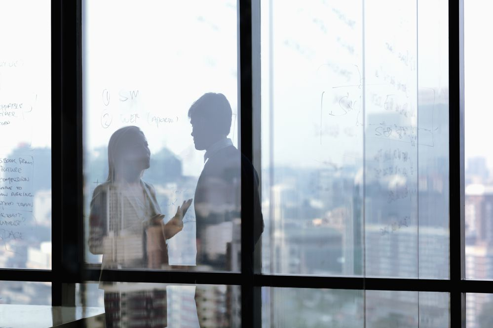 Silhouette shadows of business people talking in office. (Getty)