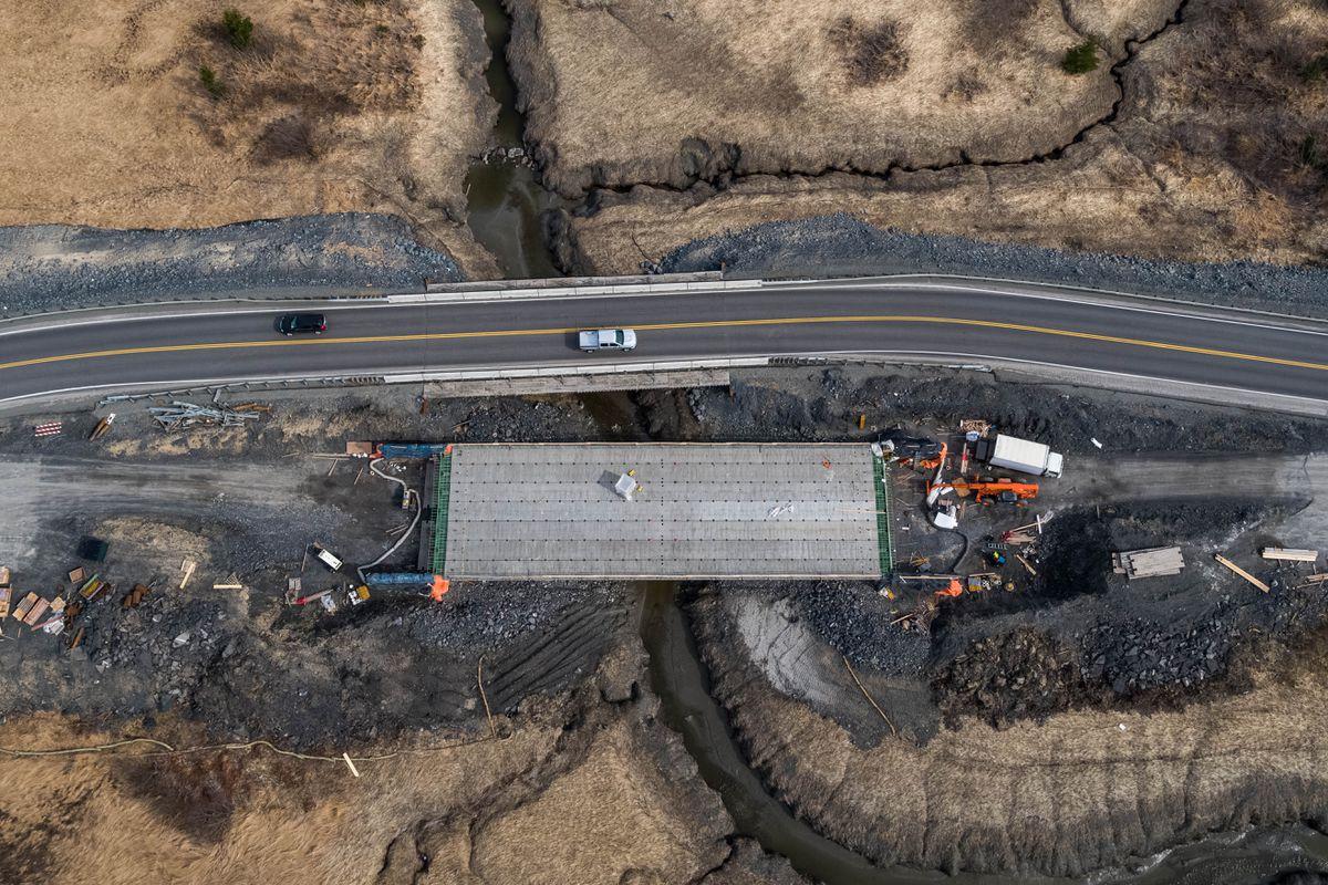 Workers replace a bridge over Virgin Creek Tuesday, April 16, 2019 on the Seward Highway near Girdwood. (Loren Holmes / ADN)