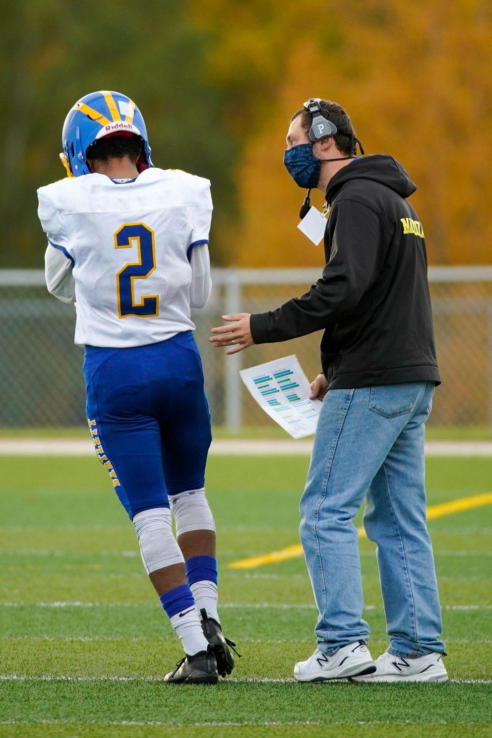 Chance Matsuoka talks with quarterback Reason Timberlake during a game against the East Thunderbirds. (Loren Holmes / ADN)