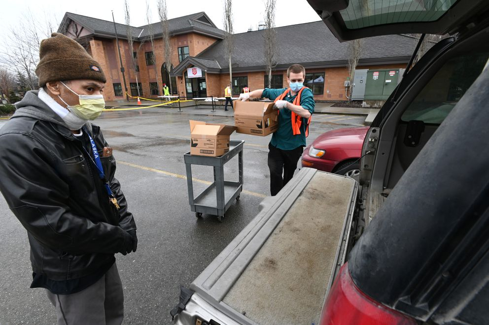 Al Mulifai watches as Benjamin Pralle delivers boxes of food for his family on the first day of The Salvation Army operating a drive-thru emergency food pantry at the McKinnell House on Tuesday, April 21, 2020. (Bill Roth / ADN)