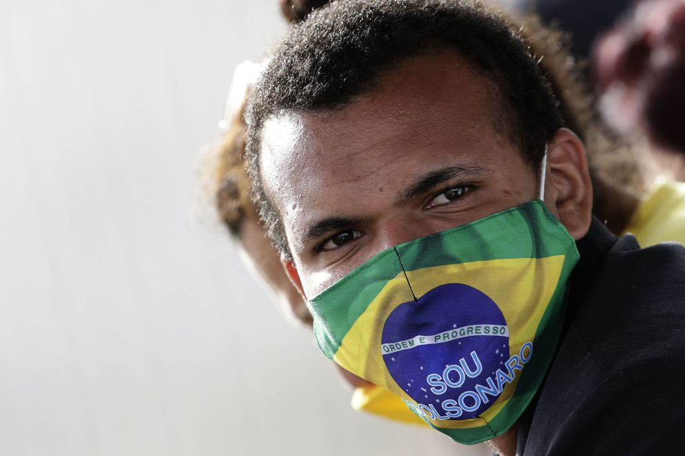 A supporter of Brazil's President Jair Bolsonaro wears mask with words written in Portuguese 'I'm Bolsonaro, ' during the president's departure from the official residence of Alvorada palace, amid the new coronavirus pandemic in Brasilia, Brazil, Monday, May 25, 2020. (AP Photo/Eraldo Peres)