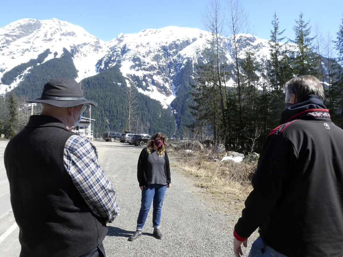 The mayor of Stewart, British Columbia, Gina McKay, center, meets with Alaska Gov. Mike Dunleavy, right, and Alaska state Sen. Bert Stedman at the U.S.-Canada border near Hyder, Alaska, on Thursday, April 22, 2021. Dunleavy said Alaska is in a fortunate position with its vaccine supply and wants to share it with people across the border in Stewart, British Columbia, a community that has close ties to Hyder. (AP Photo/Becky Bohrer)