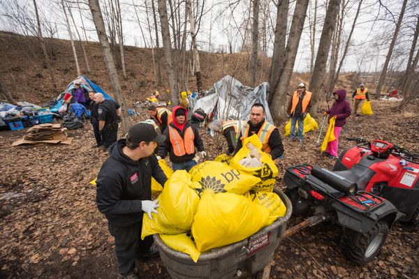 Volunteers pick up trash at a homeless camp near the Brother Francis Shelter Saturday, April 28, 2018. (Loren Holmes / ADN)