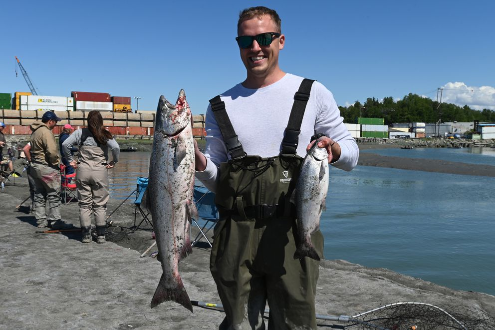Mark Steblein holds up the first two salmon he has ever caught while king salmon fishing at Ship Creek near downtown Anchorage on Sunday. Steblein caught the jack king on the right before hooking the adult chinook on the left. (Bill Roth / ADN)