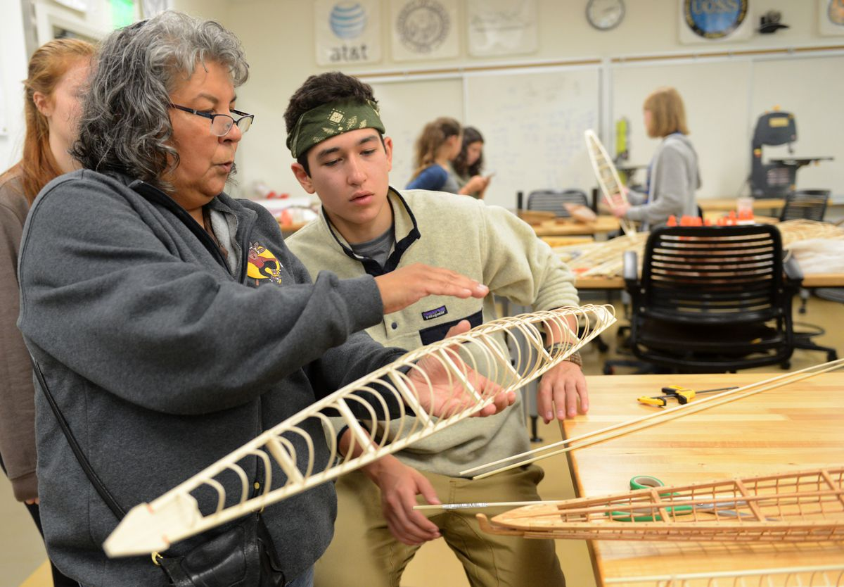 Cultural teacher Teresa Smith talks with Ethan Sundown, a sophomore from Bethel, about installing the keel on a model kayak he is building in Anchorage on Wednesday, Aug. 1, 2018. Sundown was taking part in a 5-week mathematics program at Alaska Native Science and Engineering Program at UAA. (Bob Hallinen / ADN)