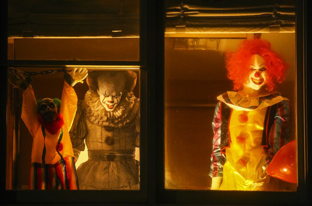 Halloween decorations, including clowns, rest in the upstairs window of a home near W. 16th Avenue and G Street in Anchorage on Oct. 28, 2020. (Emily Mesner / ADN)