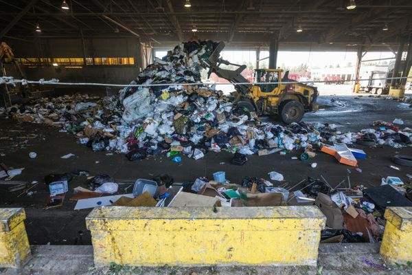 A loader moves trash around the tipping floor at the central transfer station Friday, Aug. 10, 2018. Solid Waste Services, which operates the transfer station, is closing for three weeks starting Aug. 14 for renovations including replacing the tipping floor. (Loren Holmes / ADN)