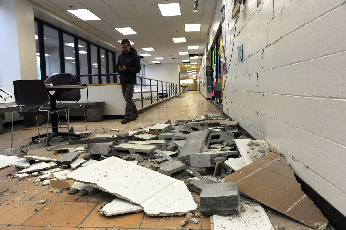 Design engineer Jason Kwiatkowski examines damage at King Tech High School, Dec. 1, 2018. The cinder block wall is not weight bearing but it and the ceiling were heavily damaged. (Anne Raup / ADN)