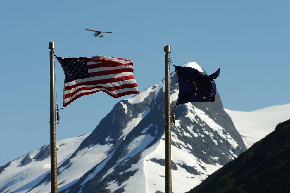 A floatplane flies out of Portage Pass over the Chugach National Forest Begich Boggs Visitor Center at Portage south of Anchorage, Alaska on Friday, July 7, 2017. The US and Alaska flags wave in the still breeze coming off of Portage Lake. (Bob Hallinen / ADN)
