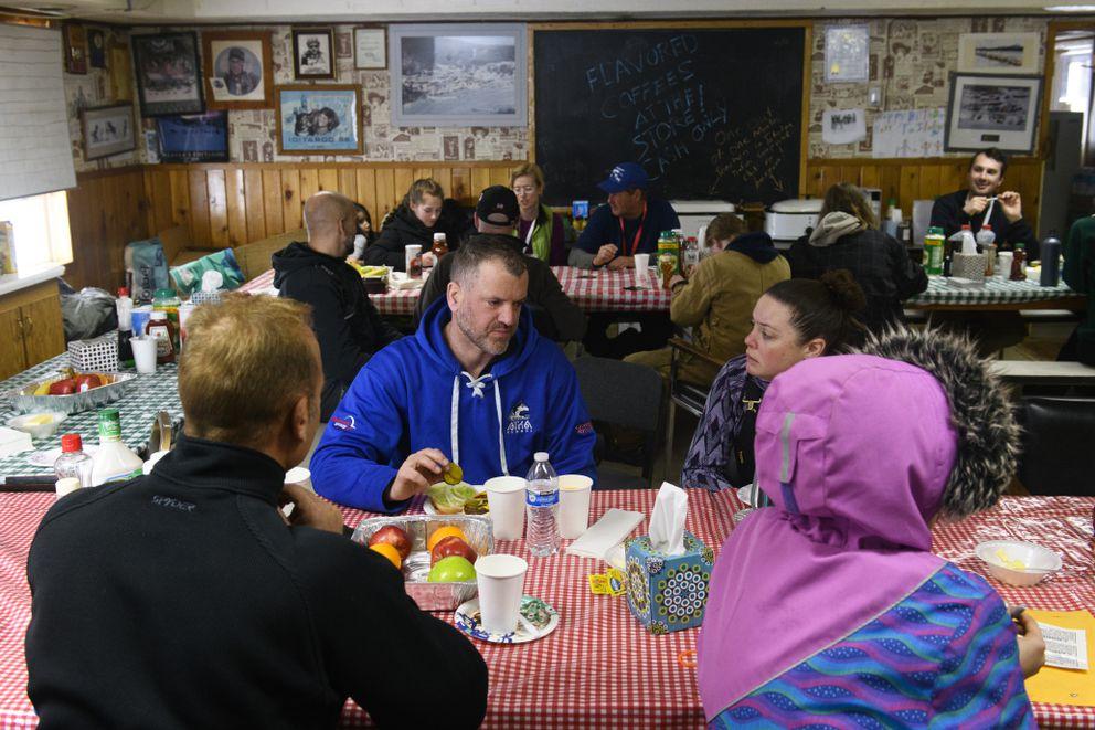 Jason Campeau talks with others inside the Takotna community hall during the 2019 Iditarod. The race will bypass the popular checkpoint this year. (Marc Lester / ADN archive)