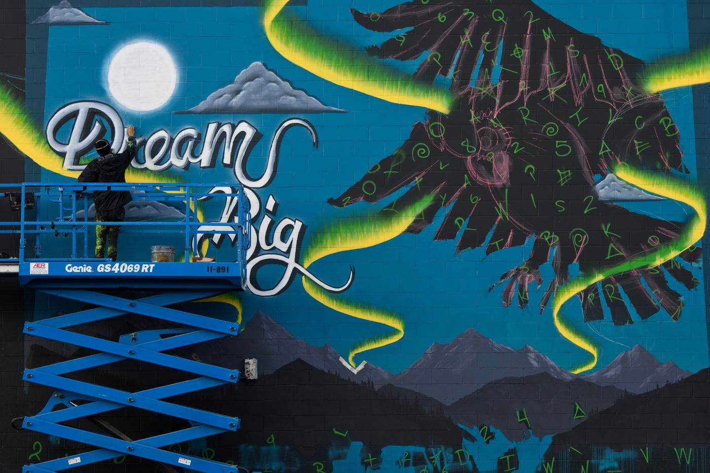 Andrew Garcia works on a large wall for the Anchorage Museum's Alaska Mural Project on October 9, 2020. (Marc Lester / ADN)