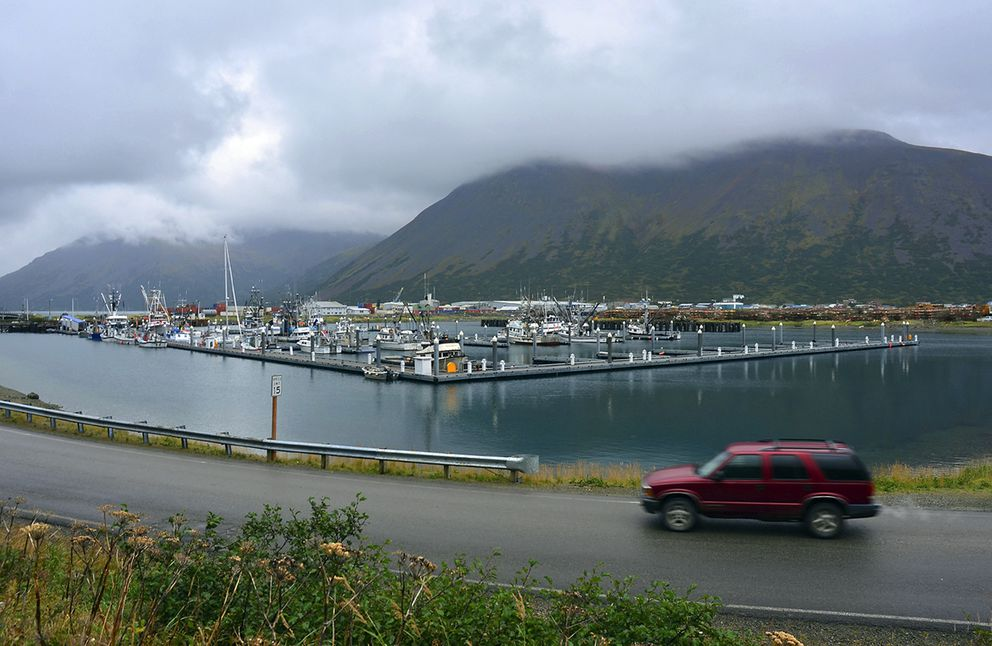 In this Sept. 23, 2013, file photo, a driver passes a small boat harbor in King Cove. (James Brooks/Kodiak Daily Mirror via AP, File)