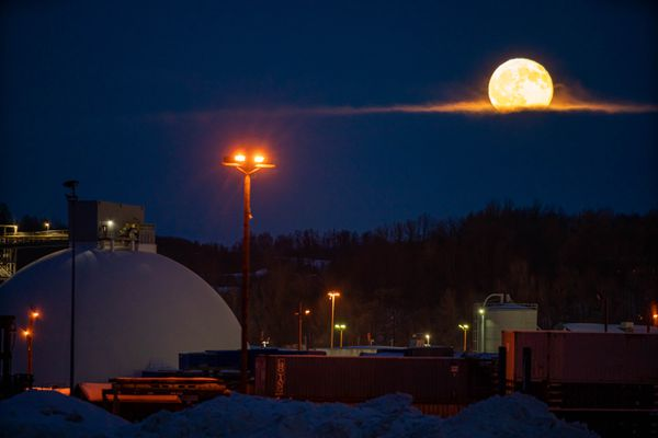 The moon rises above the Port of Alaska on Wednesday, Dec 30, 2020. The large white dome is a cement storage building. (Loren Holmes / ADN)