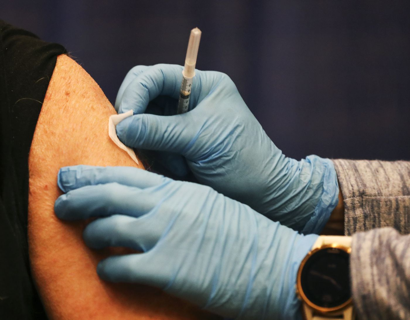 Fairweather, LLC Advanced Nurse Practitioner Jyll Green sanitizes David Stevenson's arm before giving him his first dose of the Pfizer-BioNtech COVID-19 vaccine at the Alaska Airlines Center in Anchorage on Saturday, Jan. 9, 2021. (Emily Mesner / ADN)