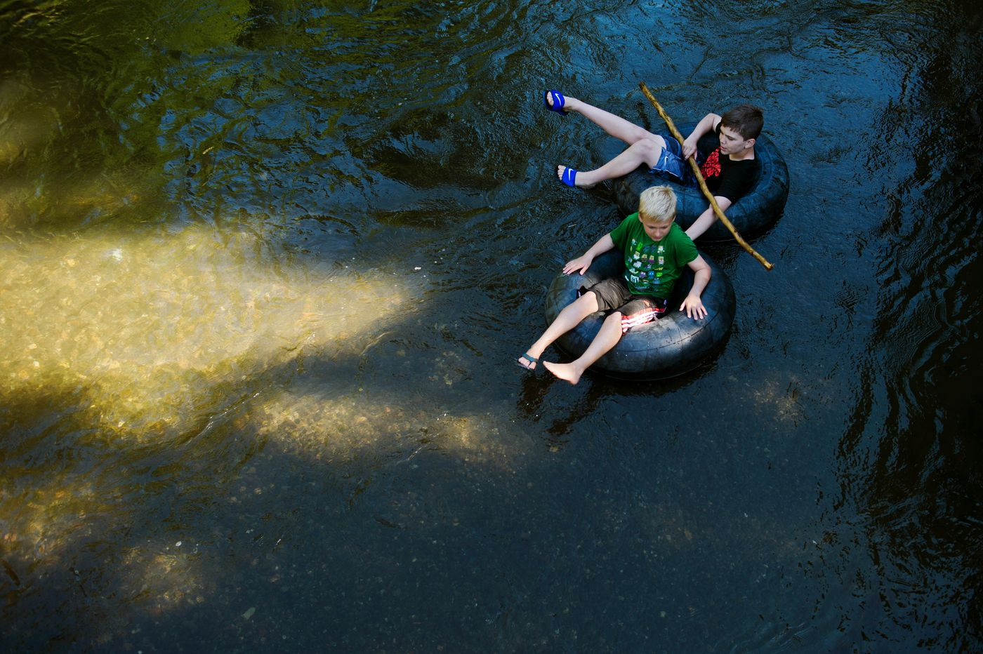 Chase Willis, 10, bottom, and Landon Sena, 13, inner tube south of Dowling Road on July 3. (Marc Lester / ADN)