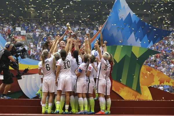 In this July 5, 2015 file photo, confetti floats down as the United States Women's National Team women celebrate with their trophy after beating Japan 5-2 in the FIFA Women's World Cup soccer championship in Vancouver, Canada. On Friday July 10, 2015, in New York, the team will make their way through swirling ticker tape up Broadway's Canyon of Heroes to a ceremony at City Hall, where they will be the first national team since 1984 and the first all-female team ever to be honored with the iconic parade.