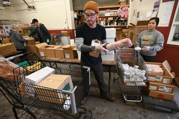 Ryan Chernikoff, a food distribution manager at the Lutheran Social Services of Alaska food pantry in Spenard, places frozen pork loin into a clients cart on Wednesday, March 18, 2020. (Bill Roth / ADN)