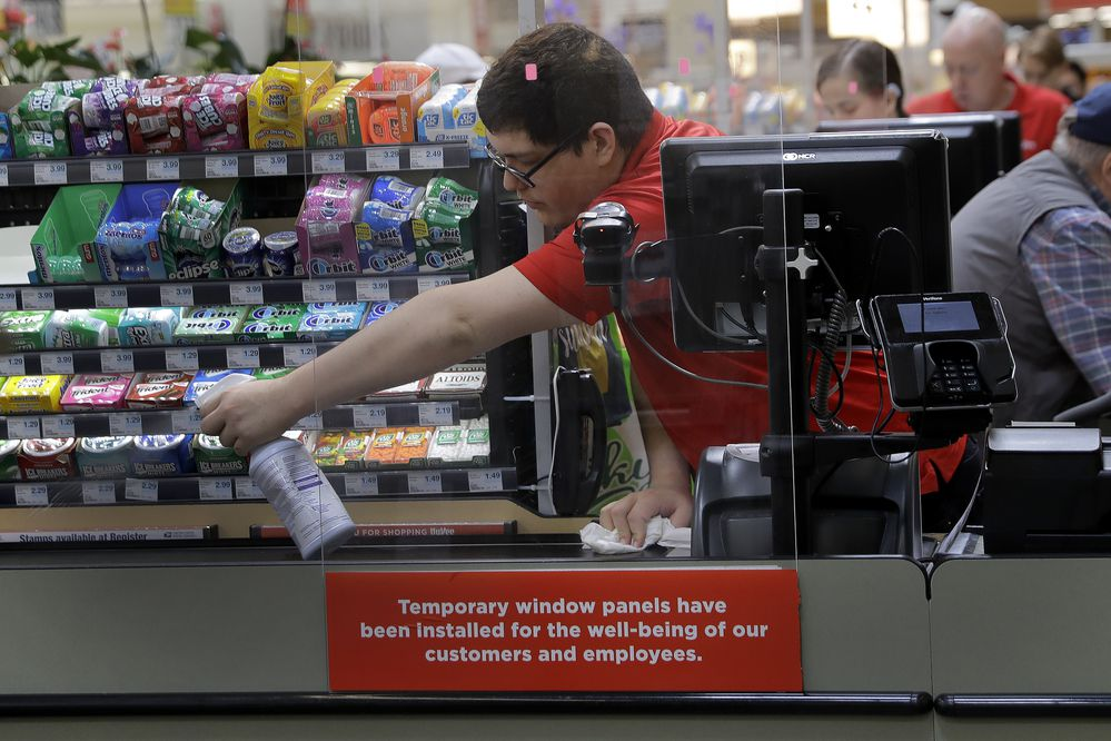 FILE - In this March 26, 2020, file photo, Garrett Ward sprays disinfectant on a conveyor belt between checking out shoppers behind a plexiglass panel at a Hy-Vee grocery store in Overland Park, Kan. From South Africa to Italy to the U.S., grocery workers — many in low-wage jobs — are manning the front lines amid worldwide lockdowns, their work deemed essential to keep food and critical goods flowing. (AP Photo/Charlie Riedel, File)