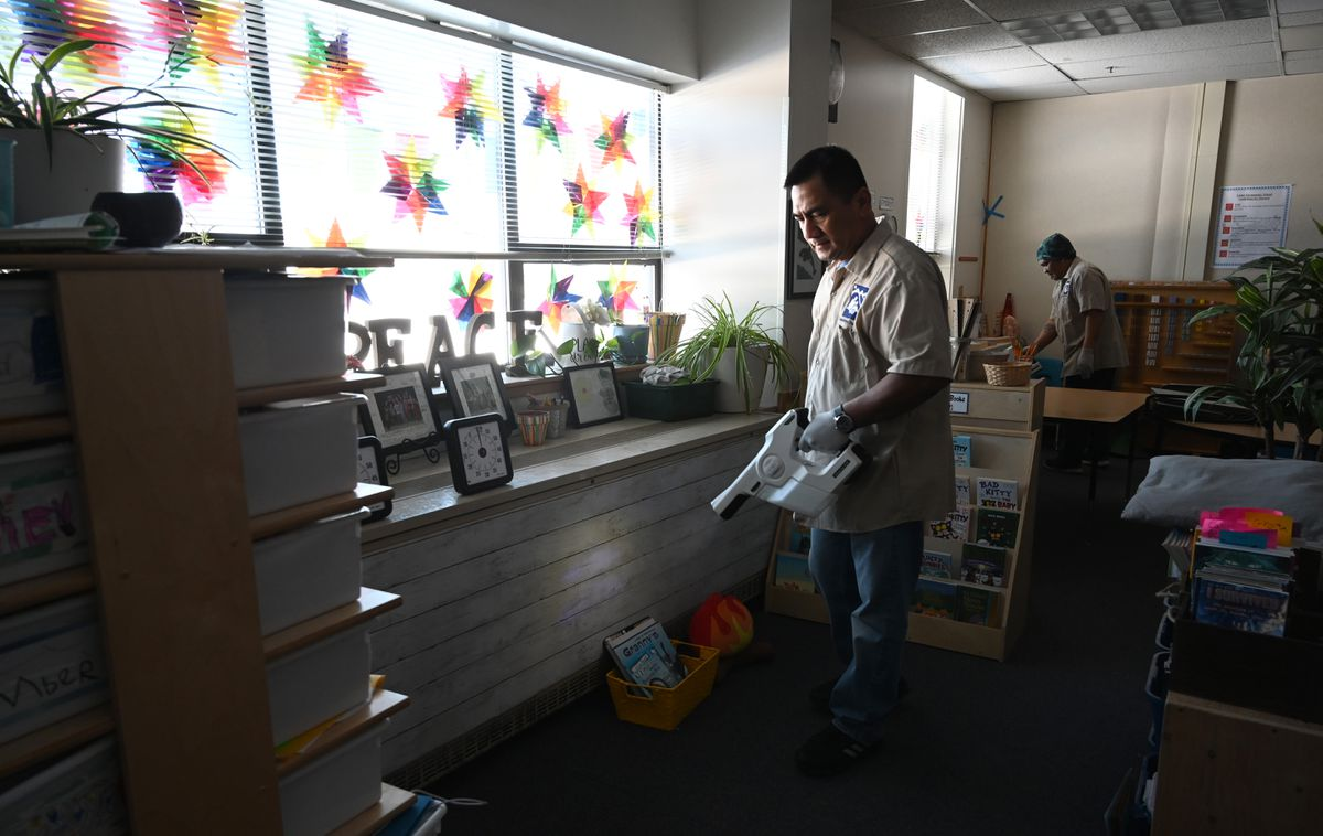 ASD custodians Rogel Parcon (left) and Jerry Tegada spray down surfaces with disinfectant in Tudor Elementary School on Tuesday afternoon. (Anne Raup / ADN)