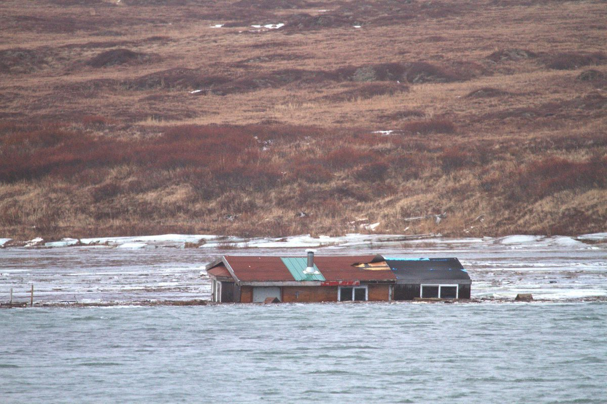 After a late-fall Bering Sea storm, one Nome cabin ended up in the Nome River and was covered by rising water. (Photo from Jim Dory via KNOM)