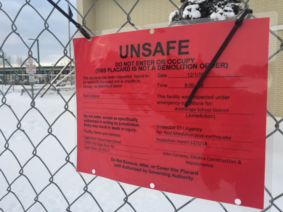 A placard outside Eagle River Elementary School warns people of 'wall collapse ' at the school, which was severely damaged in the Nov. 30 earthquake. On Tuesday, the Anchorage School District announced both Eagle River Elementary and Gruening Middle School will be closed for the 2019-20 school year. (Star photo by Matt Tunseth)