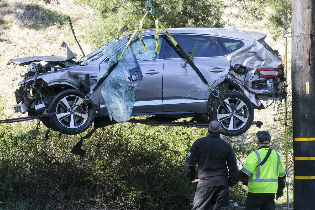 A crane is used to lift a vehicle following a rollover accident involving golfer Tiger Woods, Tuesday, Feb. 23, 2021, in the Rancho Palos Verdes suburb of Los Angeles. Woods suffered leg injuries in the one-car accident and was undergoing surgery, authorities and his manager said. (AP Photo/Ringo H.W. Chiu)