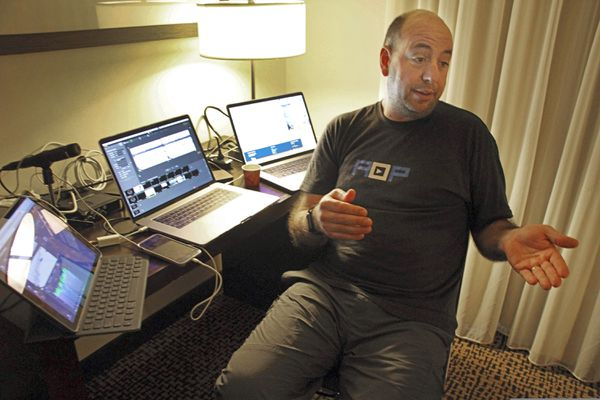 In this Tuesday, March 5, 2019 photo, Art Aldridge of New York City explains how he coordinates live video from checkpoints along the Iditarod Trail Sled Dog Race in remote parts of rural Alaska back to his master control set-up, three laptop computers set up in a darkened hotel room in Anchorage, Alaska. Far from competitors tackling the frozen wilderness in Alaska's Iditarod Trail Sled Dog Race, a dozen people, including Aldridge, are holed up inside an Anchorage hotel behind banks of computers, tracking the punishing route and connecting with global fans seeking a real-time link to the off-the-grid sport. (AP Photo/Mark Thiessen)