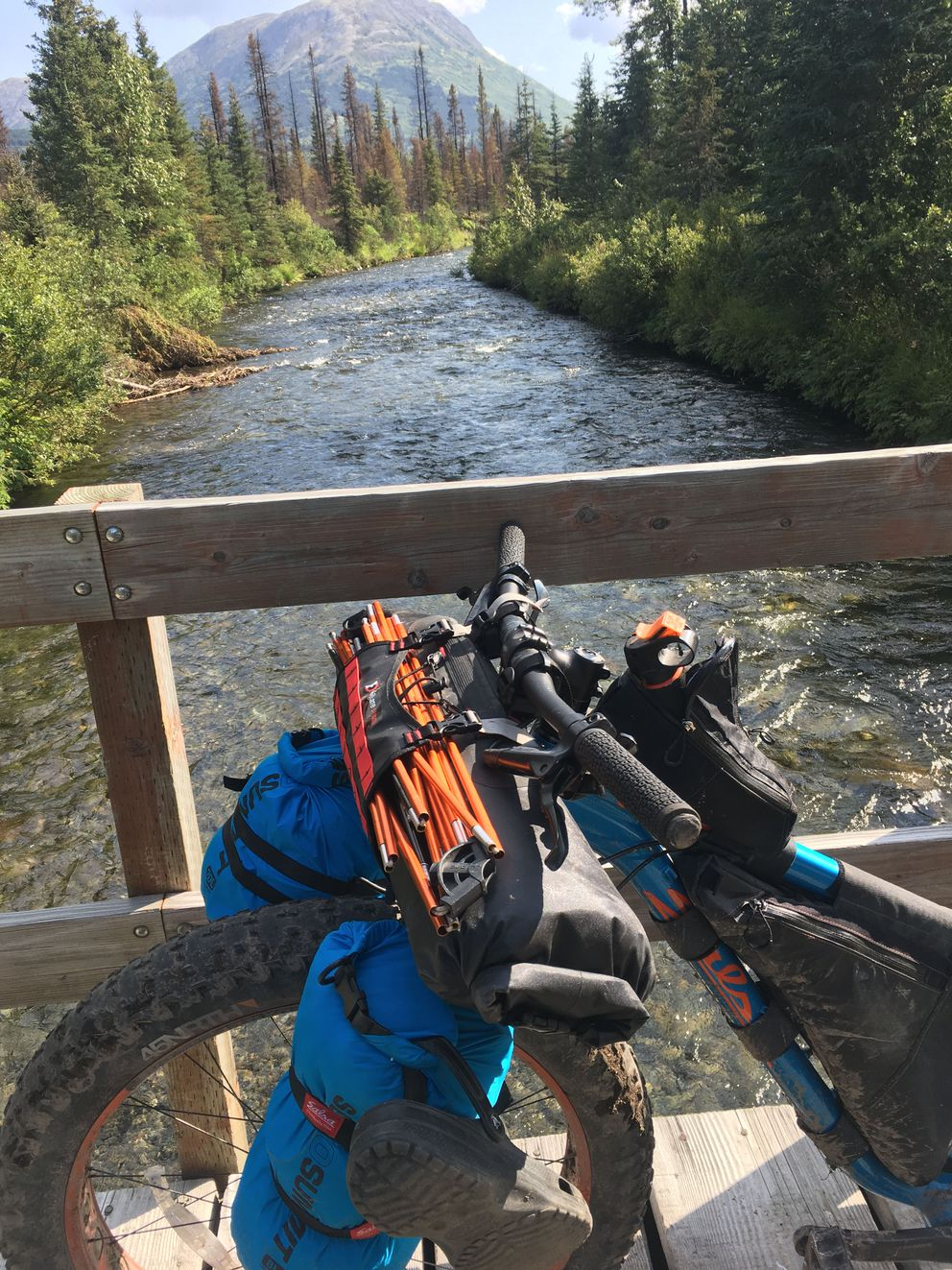 All Harvey's bike is packed for camping, complete with orange tent poles, near Trout Lake. Harvey recommends tightly rubber-banding the poles together before strapping them to the bike. (Photo by Alli Harvey)
