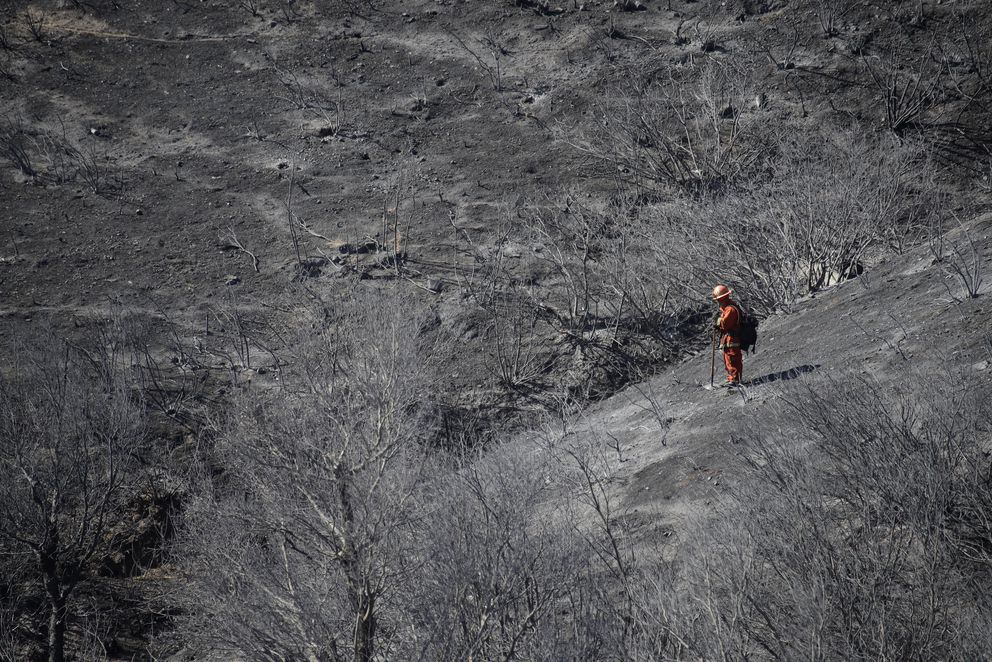 A member of a California Dept. of Corrections fire crew walks down a ridge in the aftermath of a wildfire Saturday, Oct. 12, 2019, in Porter Ranch, Calif. (AP Photo/Marcio Jose Sanchez)