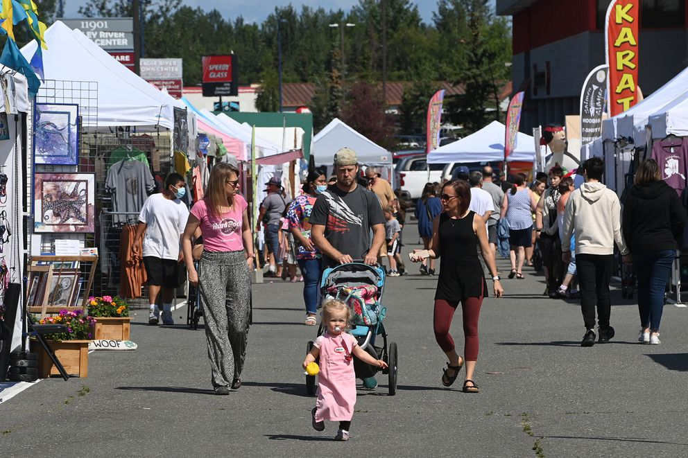 Twenty-month-old Salome Lewis leads her mother Wiola, left, and Wendel Lewis, center, through the vendor booths at the Bear Paw Festival in Chugiak-Eagle River on Thursday, July 15, 2021. (Bill Roth / ADN)