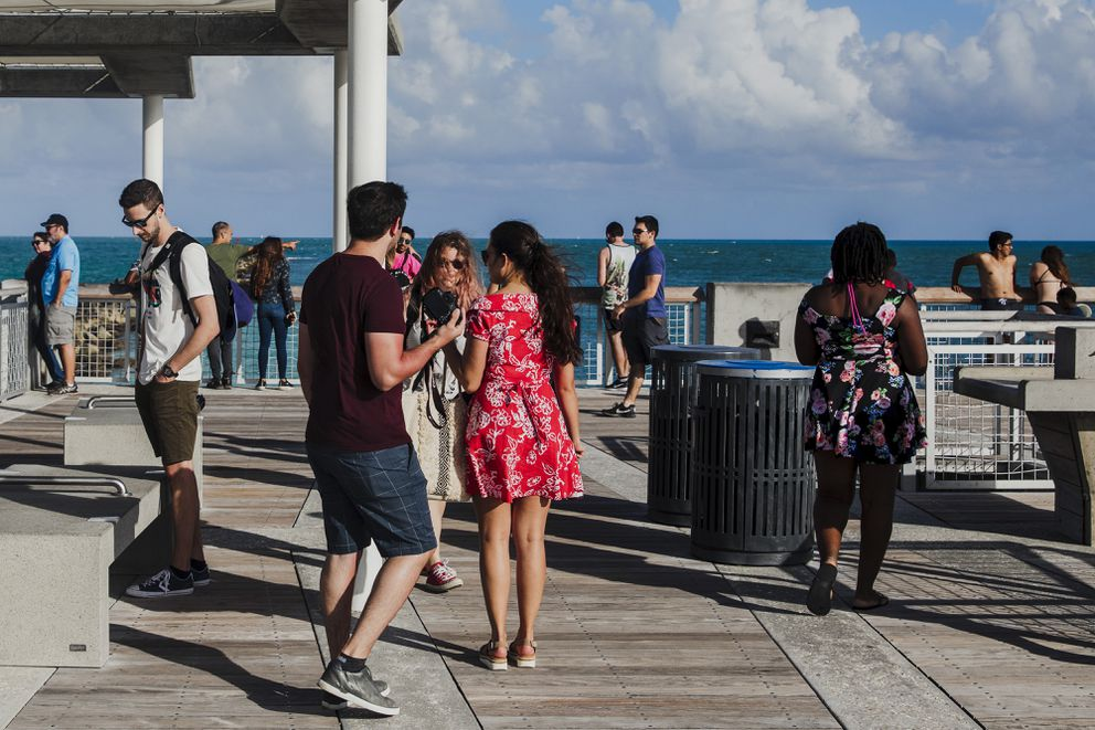 People crowd the pier at South Pointe Park in Miami Beach, Fla., on March 11. Photo for The Washington Post by Scott McIntyre