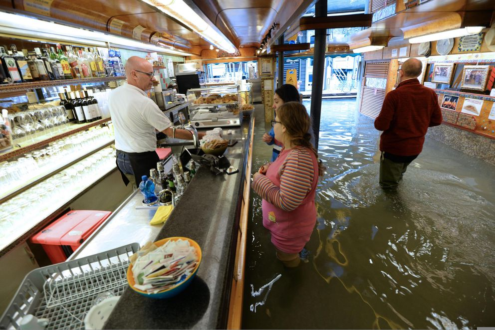 Venetian people in a bar amid rising water in Venice, northern Italy, Sunday, Nov. 17, 2019. Venetians coped with another exceptional tide Sunday in a season that is setting records while other parts of Italy wrestled with a cornucopia of weather woes, from rain-swollen rivers to high winds to an out-of-season avalanche. (Andrea Merola/ANSA via AP)