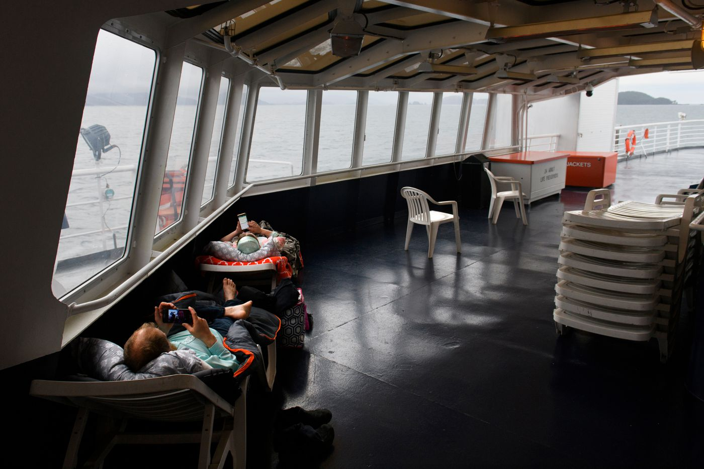 Dimitry and Zina Kuzmin recline in the solarium of the ferry Aurora. Dimitry, a Prince William Sound commercial fisherman, said cuts to the ferry system caused him to stop fishing earlier than he otherwise would have. (Marc Lester / ADN)