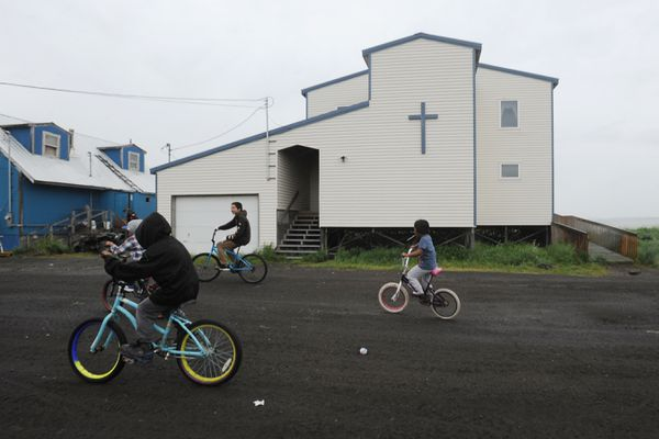Children ride bicycles past the Catholic church in the Yup'ik village of Stebbins on the Norton Sound coast in Western Alaska on Wednesday, June 26, 2019. The old church where the sexual abuse of children occurred in the 1960's was torn down and replaced with this church. (Bill Roth / ADN)