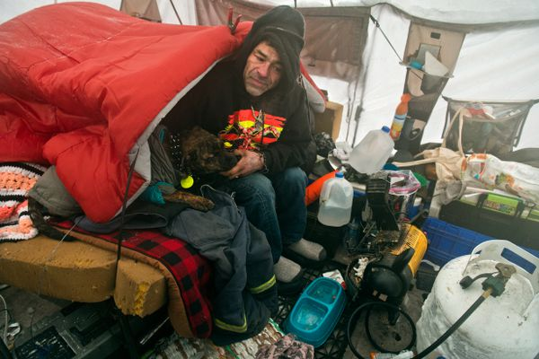 Ricardo Molina and his dog, Satan, sit next to a space heater inside a tent near 3rd Avenue and Ingra Street on January 6, 2020. Molina said there are about a dozen other homeless people in the area who sleep outside, even in the cold weather. (Marc Lester / ADN)