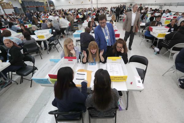 FILE- In this Friday, Nov. 16, 2018, file photo workers at the Broward County Supervisor of Elections office show Republican and Democrat observers ballots during a hand recount in Lauderhill, Fla. Florida Republican Gov. Rick Scott is leading incumbent Sen. Bill Nelson in the state's contentious Senate race. Official results posted by the state on Sunday, Nov. 18, showed Scott ahead of Nelson following legally-required hand and machine recounts. State officials will certify the final totals on Tuesday. (AP Photo/Wilfredo Lee, File)